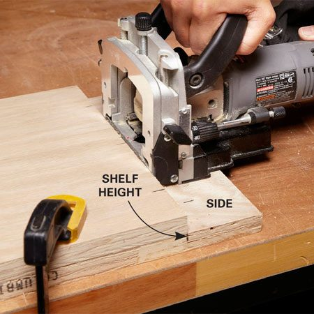 <b>Photo 2: Cut the shelf slots</b><br/>Clamp the pieces together, rest the joiner on the cabinet side and cut the slots in the shelf.