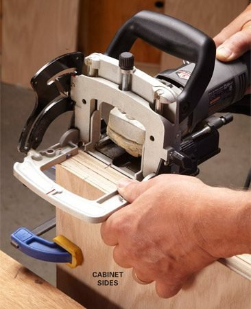 <b>Photo 6: Cut slots in the side</b></br> Hold the fence down firmly for accuracy. For the sides, give the joiner more support by clamping both sides of the cabinet together.