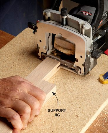 <b>Hold in place while cutting</b></br> To support the piece you're cutting, make a simple support jig from a scrap of face frame attached to a base. Keep your hands well away from the joiner, or use clamps.