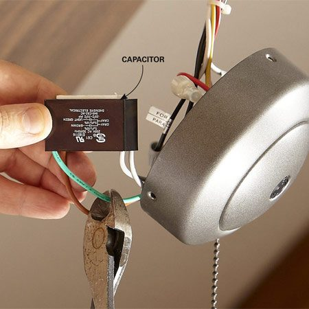 <b>Photo 1: Remove the capacitor</b></br> Reach into the housing and gently pull out the capacitor. Untangle it from the other wires. Then cut the capacitor lead wires one at a time, or remove the wire nuts and cut off the wire strands.