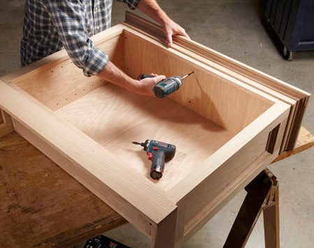 <b>Photo 12: A screwed-on top is better</b></br> <p>Mount the top with screws only—no glue. That way, you can remove it for easier sanding and finishing. Center the top and drive screws through the box lid and into the filler blocks.</p>