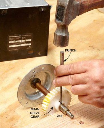 <b>Photo 2: Remove the gear from the shaft</b></br> Support the shaft on a 2x4 and use a punch to drive out the pin that holds the gear in place.