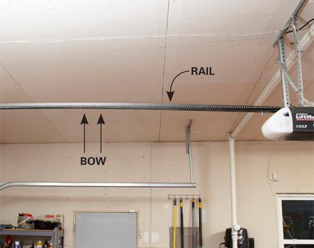 <b>Overtravel causes bow in the rail</b><br/>If you notice an upward bow in the rail, reduce the distance the door travels down. A door that travels too far down causes excess wear and tear on the opener.