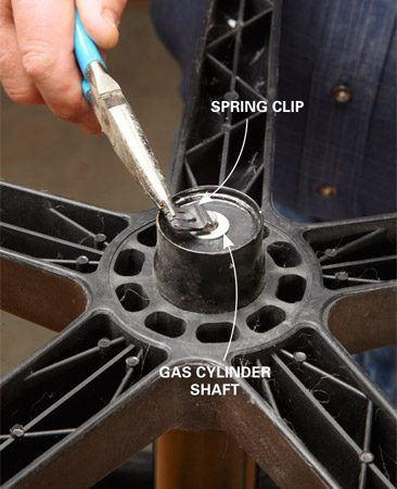 <b>Photo 1: Remove the clip and pedestal</b></br> <p>Jam a needle-nose pliers into the spring clip and pull it off. Then lift the pedestal off the chair.</p>