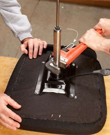 <b>Photo 3: Twist the gas cylinder</b></br> <p>Use a pipe wrench to loosen the press-fit gas cylinder (there are no threads). Then lift the cylinder out of the tilt mechanism.</p>
