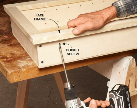 <b>Photo 7: Attach the face frame to the box</b></br> Drill pocket holes on the outsides of the cabinet box. Align the face frame and clamp it. Attach the face frame with pocket screws.