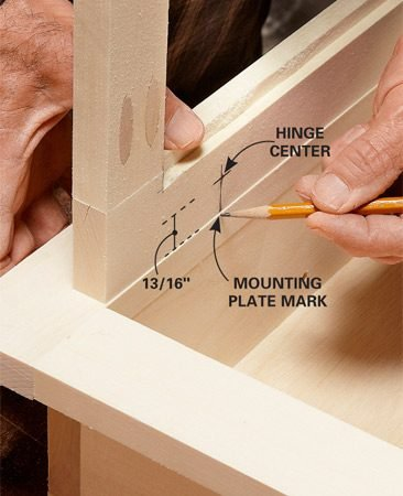 <b>Photo 6: Mark for the hinge mounting plates</b></br> Rest the edge of the door on the cabinet and center it. Then transfer the hinge center marks to the cabinet sides to indicate the center of the mounting plates.
