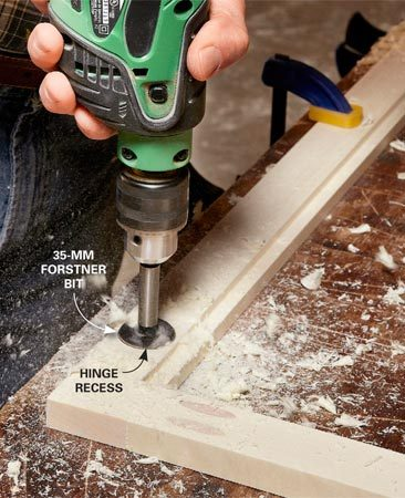 <b>Photo 8: Drill concealed-hinge mounting holes</b></br> Mark the hinge hole locations. Use an awl or nail to make a starting point for the Forstner bit. Drill recesses for the hinges in both doors.
