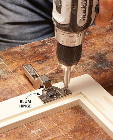 <b>Photo 9: Mount the hinges on the doors</b></br> Press the hinges into the 35-mm recesses and line them up so that the screw holes are parallel to the edge of the door. Attach the hinges with the screws provided.