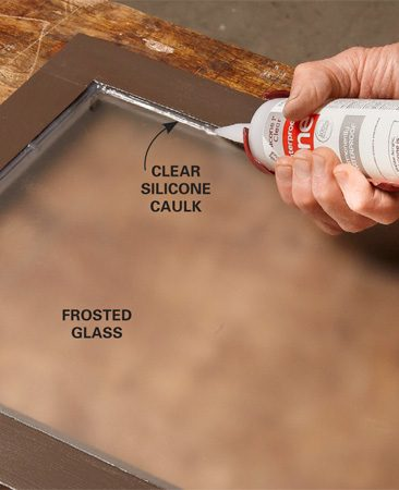 <b>Photo 10: Install the glass</b></br> After the paint dries, set the glass panels in the rabbet and apply a small, neat bead of clear silicone around the perimeter. Let the silicone cure overnight before mounting the doors.
