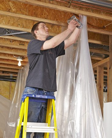 <b>Photo 1: Get ready for dust</b></br> Instead of just covering your stuff with sheets of plastic, isolate your work area with a wall of plastic sheeting. Make sure to fill in the spaces between joists.
