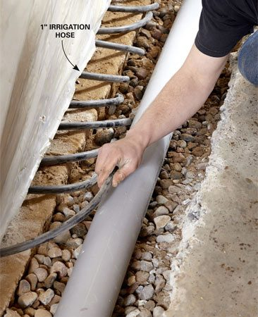 <b>Photo 5: Install hose in the block walls</b></br> Drill 1-in. holes in each block core and each mortar joint. Then insert sections of 1-in. irrigation hose from the holes into the gravel to carry away the water.