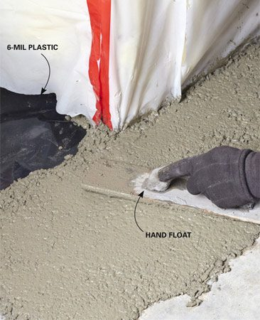 <b>Photo 6: Cap off the trench with concrete</b></br> Lay plastic over the rock and cover it with concrete. Smooth out the concrete with a float. Wait 20 minutes, and work it smooth with a steel trowel.