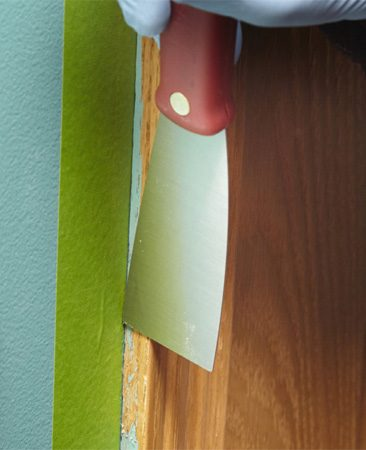 <b>Photo 1: Tape and scrape</b></br> Apply painter's tape on the wall to protect the paint. Then apply light pressure to a putty knife and scrape off the surface paint blobs.