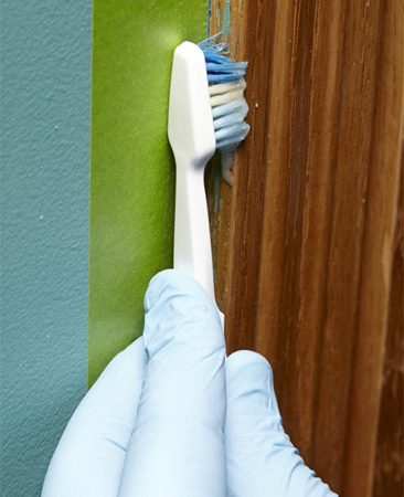 <b>Photo 2: Apply paint remover</b></br> Squirt a few drops of paint remover onto an old toothbrush and brush in the direction of the wood grain.