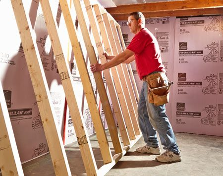<b>Tip up the walls</b></br> If the floor joists are sagging or there's ductwork in the way, you may have to lift the top of the wall in first and slide the bottom plate into place as shown here.