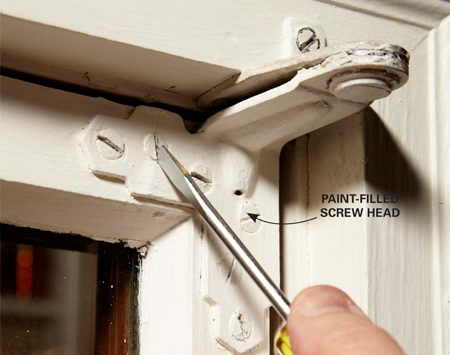 <b>Photo 4: Chip out the paint</b></br> Tilt a flat-blade screwdriver at a 45-degree angle and hammer it along the slotted head to chip out the paint. Then slice through any remaining paint with a utility knife.