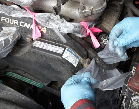 <b>Photo 1: Protect everything electrical</b></br> Wrap ignition wires and coils and all electrical connectors with plastic wrap. Then add a flag of fluorescent surveyor's tape so you don't forget to remove the wrap later.