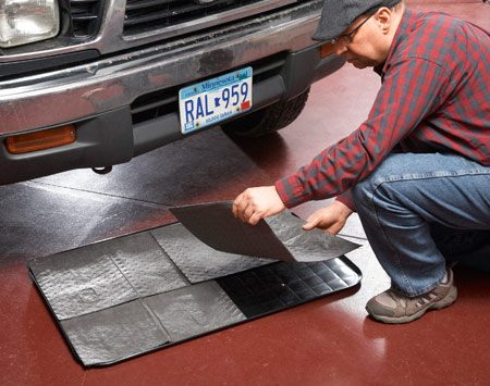 <b>Photo 2: Soak up the hazardous waste</b><br/>Spread absorbent mats on a drip pan and slide the pan under the engine.