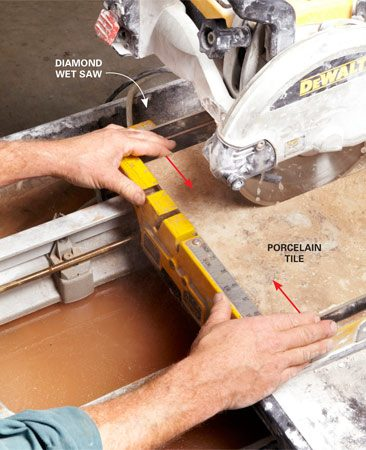 <b>Diamond wet saw technique</b></br> You'll need a diamond wet saw to cut large porcelain tiles. Dean recommends renting a contractor-quality saw rather than buying a cheapie. But even with a saw like this, tiles larger than about 8 in. square have a tendency to crack before you finish the cut, often ruining the tile. You can help prevent this by pressing the two pieces together as you near completion of the cut. Holding the tile like this stabilizes it and dampens vibration, resulting in a cleaner cut.