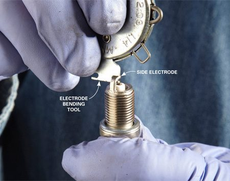 <b>Opening and closing the gap</b></br> Hook the adjusting tool onto the side electrode and pry it up slightly. Then recheck the gap. To close the gap, simply push the electrode down instead of pulling it up. Always recheck the gap after making adjustments.