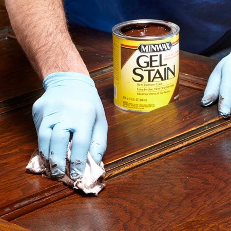 Touching up old woodwork by wiping on stain with a rag.