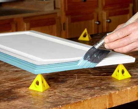 <b>Work faster with pyramids</b></br> <p>These handy plastic pyramids hold your project off the surface  so you can paint the edges easily. Better yet, you can finish the front of  doors (or the top of shelves) without waiting for the back to dry. Paint the  back of the door and set it painted side down on the pyramids while you paint  the front. The sharp points on the pyramids will leave only little spots on the  wet paint, and they're easy to touch up later.</p> <p>You'll find plastic pyramids at home centers, paint stores and  hardware stores. A pack of 10 costs only a few dollars.</p>