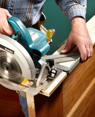 <b>Photo 4: Trim the jamb with a circular saw </b></br> You can also use a circular saw to cut down jambs when they need it. Install an 80-tooth blade to prevent tearing out the wood veneer. It's easy to cut off the wrong jamb, so make sure you cut the jamb that rests on the high side of the floor. It's the one on the opposite side of the opening where you marked your shim. A rafter square works great as a saw guide.