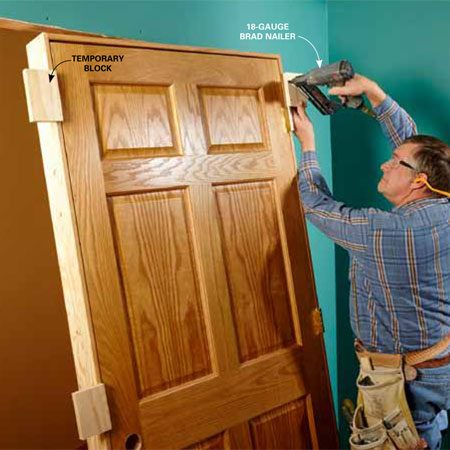 <b>Photo 7: Attach temporary blocks to the jamb</b></br> To hold the doorjamb flush with the drywall before permanently fastening it, attach temporary blocks to both sides of the jamb. Use scrap lumber to make five 4-in. to 5-in. blocks, and attach each with 2-in. 18-gauge brads. Nail three blocks on the latch side and two on the hinge side (the door slab keeps the middle of the hinge side rigid). Keep the blocks away from the hinges so they won't interfere with shimming. The casing will cover up the nail holes when the blocks are removed.