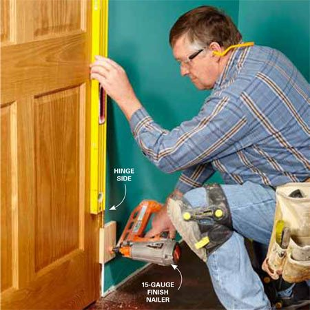 <b>Photo 9: Nail the blocks to the wall</b></br> <p>Set the door in the center of the opening. Make sure you have a  consistent gap between the door slab and all three sides of the jamb. If the  bottoms of the jambs were properly cut beforehand, the gaps will be consistent,  the top jamb will be level and the sides will be plumb.</p> <p>Double-check the hinge side for  plumb before nailing the blocks to the wall with a couple of 2-in., 15-gauge  finish nails. Nail the hinge side first, and then recheck the gap around the  door slab before fastening the blocks on the latch side. The blocks will allow  enough wiggle room for fine-tuning before the jamb is shimmed and nailed to the  framing.</p>