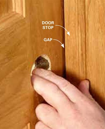 <b>Photo 11: Check gap at stops</b></br> Before installing any shims, remove the plug that holds the door slab in place, and make sure the door opens and closes properly. The door should come in contact with the door stop evenly the whole length of the stop. If one side of the door hits the stop first, you'll have to adjust the jambs by moving either the top side or the bottom side of the jamb in or out, depending on which part of the door hits first.