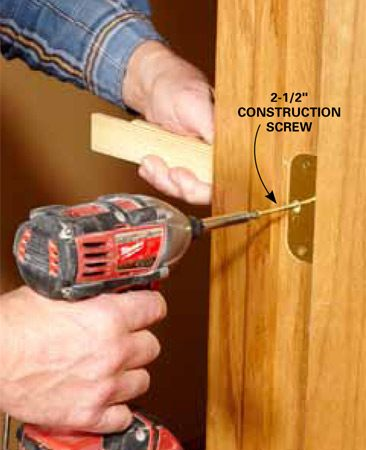 <b>Photo 14: Install longer screws in each hinge</b></br> <p>Replace one factory screw in each hinge with a longer screw.  Drive the screw in very slowly the last few turns, and pay close attention to  the jamb. You don't want to suck the jamb in and throw off the alignment of the  door. Check all the gaps, and open and close the door after you install each  screw.</p> <p>Make sure the screws penetrate the framing a minimum of 1 in.  The gap between the framing and this doorjamb was about 1/2 in., so we  installed 2-1/2-in. screws. Don't use drywall screws—they're brittle and won't  hold up to years of abuse. Buy construction screws instead, and try to find one  that's close to the same color as your hinges.</p>