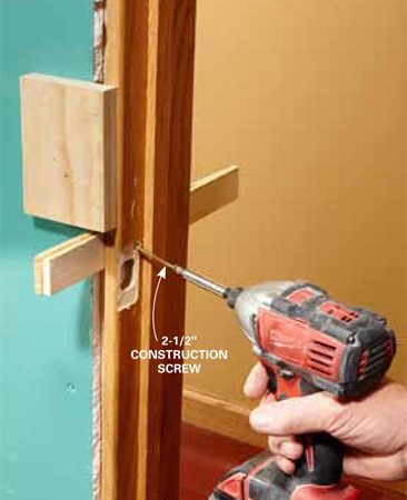 <b>Photo 15: Secure the latch side</b></br> <p>Insert and secure shims 4 in. down from the top of the door and  4 in. up from the floor. Nail the shims the same way that you did on the hinge  side.</p> <p>We have repaired doors that were  slammed shut so violently from the wind that the jamb on the latch side was  knocked several inches out of place. To prevent this problem, install a long  construction screw behind the latch plate. Predrill and countersink a hole in  the corner of the latch plate space so it won't interfere with the latch plate  screws. Don't use longer screws in the latch plate holes because they're too  close to the edge and can split the framing lumber.</p>