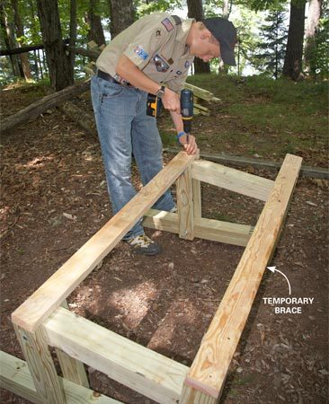 <b>Photo 3: Brace the legs</b></br> Cut the three untreated 2x4s to 4 ft. and screw them to both ends of the feet and the front of the seat supports. They'll serve as temporary braces while you attach the bench seat and backrest boards.