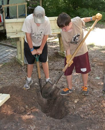 <b>Photo 6: Dig the trenches and install your bench</b></br> <p>Position and mark the trenches and dig them about 8 in. deep. Rest the bench in the trenches. Check the bench for level and height, then remove it and adjust the soil levels as necessary. Pour 1-1/2 bags of concrete mix beside, between and over each base and cover with soil. Pour a couple of gallons of water over the dry mix and backfill the trenches.</p>