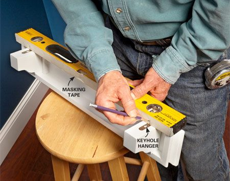 <b>Mark; don't measure</b></br> Place a strip of masking tape on one edge of your level and mark the center of each keyhole on the tape.
