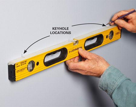 <b>Transfer to the wall</b></br> Hold the level against the wall at the height you want the shelf. Remember that the top of the shelf will be above your marks. Adjust the level until the bubble is centered, and mark the keyhole locations on the wall. Then install anchors or drive the screws into the studs and hang the shelf.