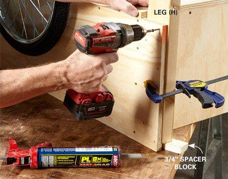 <b>Photo 5: Install the legs</b></br> Apply two beads of construction adhesive, clamp the legs into place and secure them with screws. The spacer block positions the leg, leaving room for the tool rack.