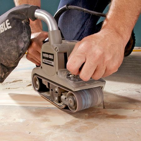 <b>Photo 1: Sand down the high spots.</b></br> Grind down any humps, lumps or bulges in the subfloor. Use the coarsest sanding belt you can find, such as 40- or 60-grit.