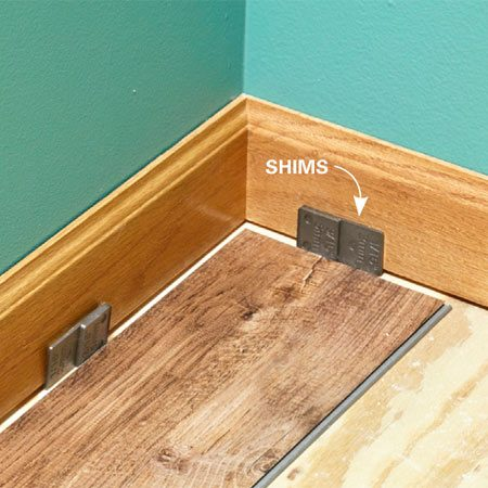 <b>Photo 4: Leave gaps along walls.</b><br/>Insert shims to create gaps. These gaps allow the flooring to expand freely with temperature changes.