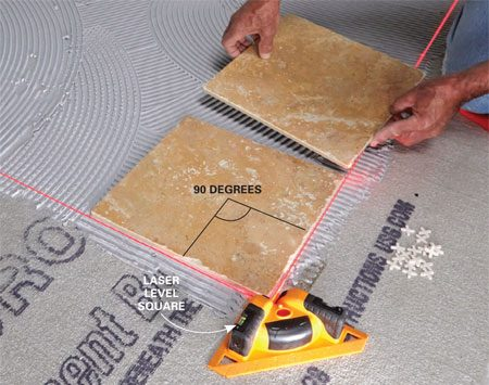Using a laser-level square for tile layout.