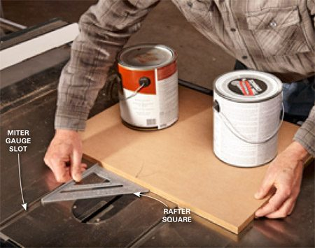<b>Photo 2: Square the base</b></br> <p>Rest two paint cans on the table and use a rafter square and the miter gauge slots to square the miter table to the table saw. Let the glue set up for 20 minutes or so. Then give the sled a test slide. If it binds at all, flip it over, clean off any glue squeeze-out and use a sanding block to knock down the edges of the runners.</p>