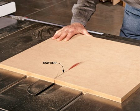 <b>Photo 3: Cut a centerline</b></br> <p>Cut a saw kerf about one-third of the way through the miter table. Turn off the saw and let the blade come to a stop. You'll use the kerf to line up the fence for the next step.</p>