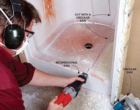 Cutting out a fiberglass shower with a reciprocating saw during bathroom demolition.
