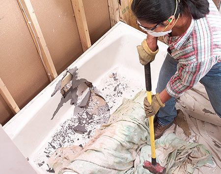 Breaking a cast iron bathtub into pieces with a sledgehammer during bathroom demolition.