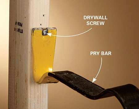 Pulling a drywall screw with a prybar when removing a wall.