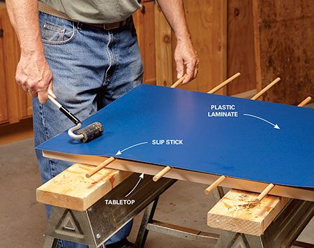<b>Photo 4: Laminate the top</b></br> <p>Wrap the top with hardwood edging, spread on contact cement and apply the plastic laminate. Slip sticks let you center the laminate before lowering it onto the top. Once the laminate makes contact with the top, it's permanently stuck; there are no second chances.</p>