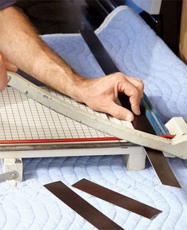 <b>Photo 4: Cut the veneer to length</b><br/><p>A paper cutter is the perfect tool for this. Measure the length of the stile and mark the strip of veneer. Line up the mark with the paper cutter blade and cut the strip to length.</p>