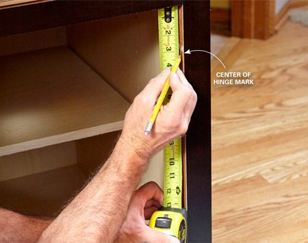 <b>Photo 7: Measure for the hinge location</b></br> <p>Mark the center of the hinge on the face frame stile. Calculate this distance by measuring from the top of your new door to the center of the hinge and subtracting the overlay.</p>
