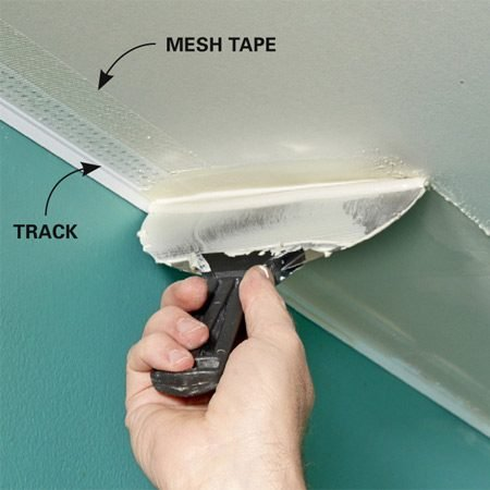 <b>Photo 8: Mud the bead</b></br> Skim joint compound over the bead, using the track to guide your knife. Mesh tape isn't essential, but it's cheap insurance against cracks.